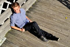 Teenager sitting along the side of a bridge Royalty Free Stock Photography