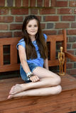 Teenager sitting on a bench. Teenage girl plays with a wooden jointed  doll stting on a bench Royalty Free Stock Photo