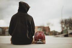 Teenager sitting in a black sweatshirt holding a skateboard on a slum background urban Stock Photography