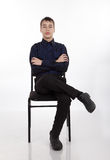 Teenager sitting on a chair Stock Image