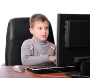 Teenager sitting  with computer monitor. Teenager sitting in armchair with computer monitor Royalty Free Stock Image