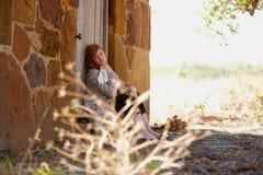 Teenager sitting in doorway. Teenage girl sitting in the doorway of a stone building Royalty Free Stock Photos