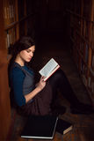 Teenager sitting on a floor of library and read. Royalty Free Stock Photos