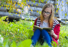 Teenager sitting in forest and reading book. Teenager girl in red jacket and glasses sitting in autumn forest and reading a book Stock Image