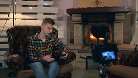 Teenager sitting in front of home video camera and speaking something during shooting. His has tablet in his hand and sits near the fireplace stock video