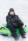 Teenager sitting on green tubing Royalty Free Stock Image
