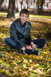 Teenager sitting on the ground Royalty Free Stock Photos
