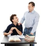 Teenager sitting at his desk while talking to his father Royalty Free Stock Photos