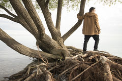 Teenager sitting on log and thinking Stock Image