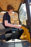 Teenager sitting in a mini digger. Cab stock photo