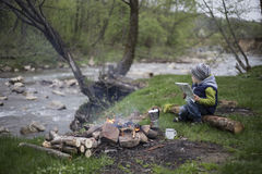 Teenager sitting near a fire in camping and watching map Stock Photo