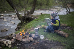 Teenager sitting near a fire in camping and watching map Royalty Free Stock Photography