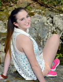 Teenager Sitting on Rocks Stock Images