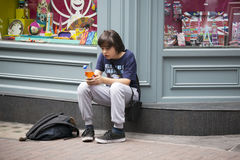 Teenager sitting on the sidewalk near the store, waiting for friends Stock Photography
