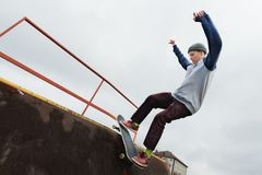 A teenager skateboarder in a hat does a Rocks trick on a ramp in a skate park against a cloudy sky and sleeping area. The concept of urban style in sport Royalty Free Stock Image