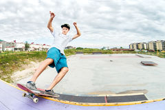 Teenager skater in a cap and shorts on rails on a skateboard in a skate park Royalty Free Stock Photo