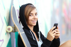 Teenager skater girl using a smart phone looking at camera. Leaning in a wall with graffiti Stock Image