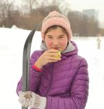Teenager skier girl with skies having drink tea brake. On snow winter park background royalty free stock image