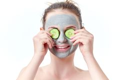 Teenager skincare concept. Young teen girl with dry clay facial mask covering her eyes with two slices of cucumber smiling Royalty Free Stock Images