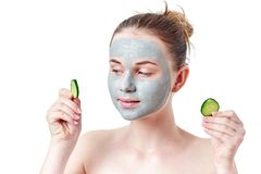 Free Teenager Skincare Concept. Young Teen Girl With Dry Clay Facial Mask Holding Two Slices Of Cucumber Stock Images - 101105284