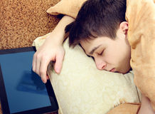 Teenager sleep with Tablet. Tired Teenager sleep on the Bed with Tablet Computer Royalty Free Stock Images