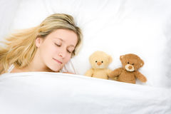 Teenager sleeping with teddies Royalty Free Stock Photography