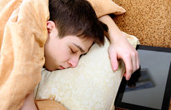 Teenager sleeps with Tablet. Tired Teenager sleeping on the Bed with Tablet Computer Stock Photo