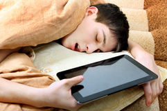 Teenager sleeps with Tablet. Tired Teenager sleeping on the Bed with Tablet Computer Stock Photography