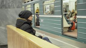 A teenager with a smartphone in his hands sits on a bench in a subway station. The guy in winter clothes is sitting in stock video footage