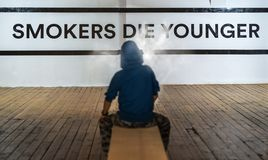 Teenager smoking and message on wall - Smokers die younger. No smoking concept stock images