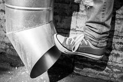 Teenager in sneakers kicks drainpipe, black and white Royalty Free Stock Images