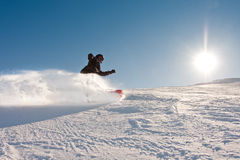 Teenager or snowboard. Teenage boy riding a snowboard downhill in sunny weather, spraying snow as he turns royalty free stock photography