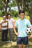 Teenager with soccer ball. Portrait of Asian teenager with soccer ball, his father and grandfather in background Stock Photography