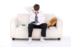 Teenager on the Sofa. Teenager reads the book on the Sofa. Isolated on the white Stock Photography
