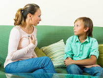 Teenager son and mother having serious talking. In home interior royalty free stock images