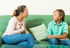 Teenager son and  mother having serious talking. On sofa in home Stock Image