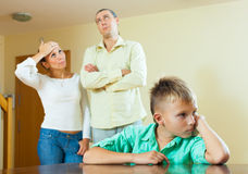 Teenager son and parents after quarrel at home. Focus on boy Royalty Free Stock Photos