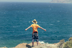 Teenager standing on a cliff Royalty Free Stock Photos