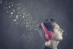 Teenager standing in front of a blackboard. With musical notes drawn and listening to music on headphones Royalty Free Stock Photography