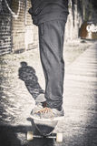 Teenager standing on a long board Royalty Free Stock Photos