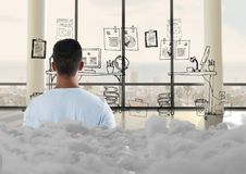 Teenager standing looking at doodle in office with clouds behind him. Digital composite of Teenager standing looking at doodle in office with clouds behind him stock photo