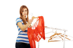 Teenager standing next to empty hanger and holding only blouse Royalty Free Stock Photography