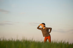 The teenager is standing in the tall grass at sunset Stock Images