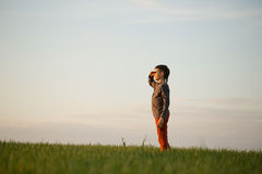The teenager is standing in the tall grass at sunset Royalty Free Stock Images