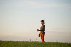 The teenager is standing in the tall grass at sunset Stock Photos