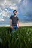 Teenager standing in a wheat field at sunset Stock Photo