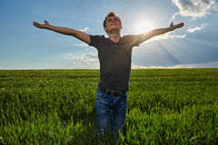 Teenager standing in a wheat field at sunset Stock Photos