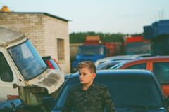 Young man with car. Teenager stands next to the cars in the parking lot Royalty Free Stock Image