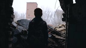 A teenager stands in the ruins of a house. Everything is destroyed