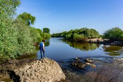 The teenager stands on top of a large stone boulder on the bank. Of the Sorraia River and looks at the river below. The river Sorraia in the summer - bright Royalty Free Stock Photos